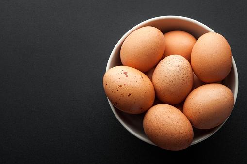 Bruine Eieren In Kom Geïsoleerd Op Donkere Achtergrond Bovenaanzicht Stockfoto en meer beelden van Biologisch