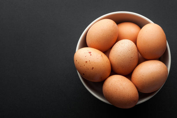 brown eggs in bowl isolated on dark background. top view brown eggs in bowl isolated on dark background. top view animal egg stock pictures, royalty-free photos & images