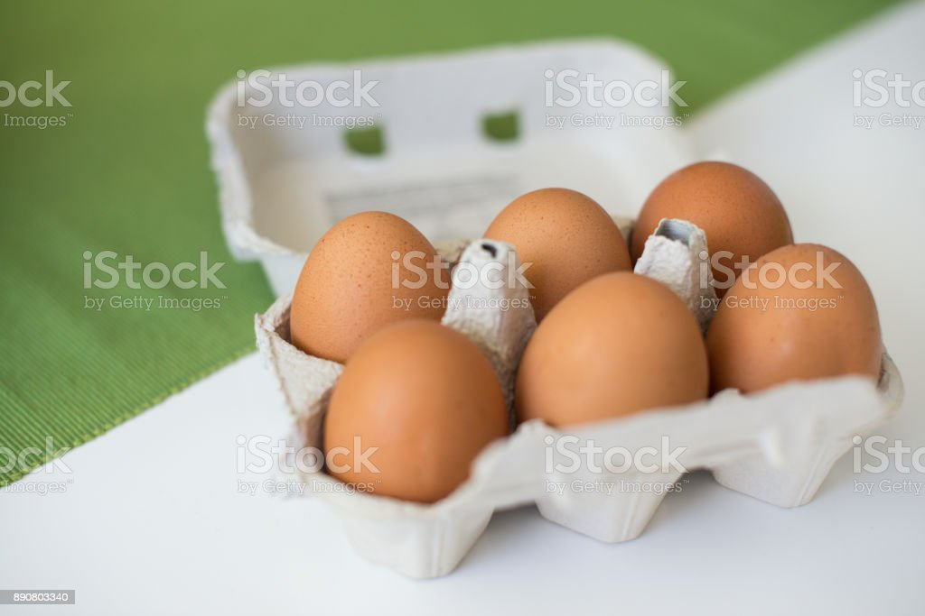 Brown eggs in carton. Close-up view of raw chicken eggs. Concept of...