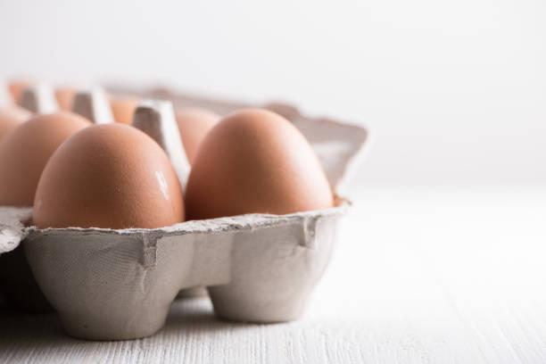 braune eier in kartonverpackung - eierverpackung stock-fotos und bilder