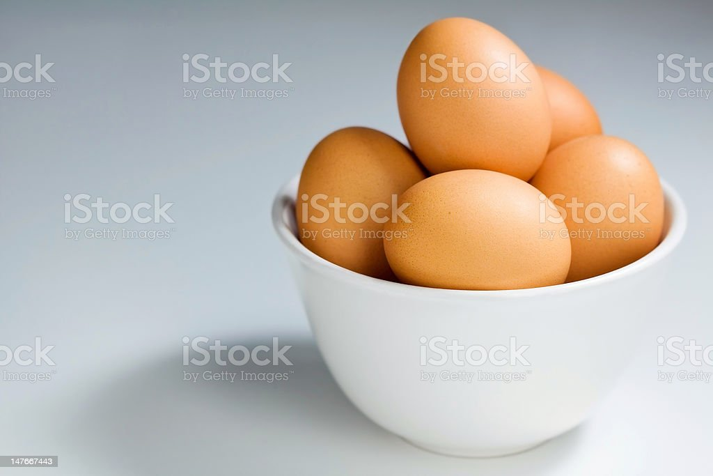 Brown Eggs in White Bowl on Pale Blue Grey Background royalty-free stock photo