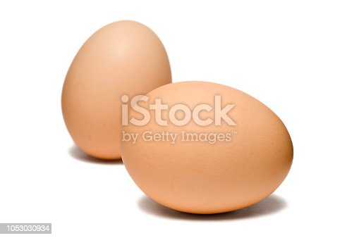 Two brown eggs isolated on a white background.