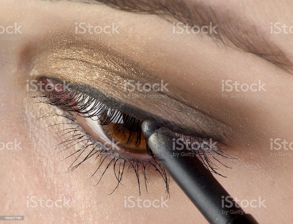 Brown eye being lined with black eyeliner pencil stock photo