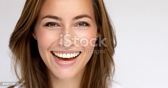 Beautiful brown eyed girl smiling in studio, portrait