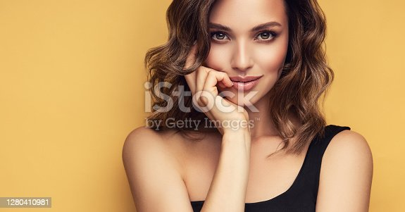 istock Brown eyed woman is looking tenderly at viewer. Make up, hairdressing and emotions. 1280410981