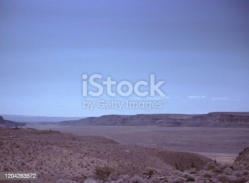 Vernacular photograph taken on a 35mm analog film transparency, believed to depict brown field under blue sky during daytime, 1965. Major topics/objects detected include Sky, Desert, Landscape, Plain, Valley, Steppe, Mountain, Hill, Sand and Nature. (Photo by Smith Collection/Gado/Getty Images)