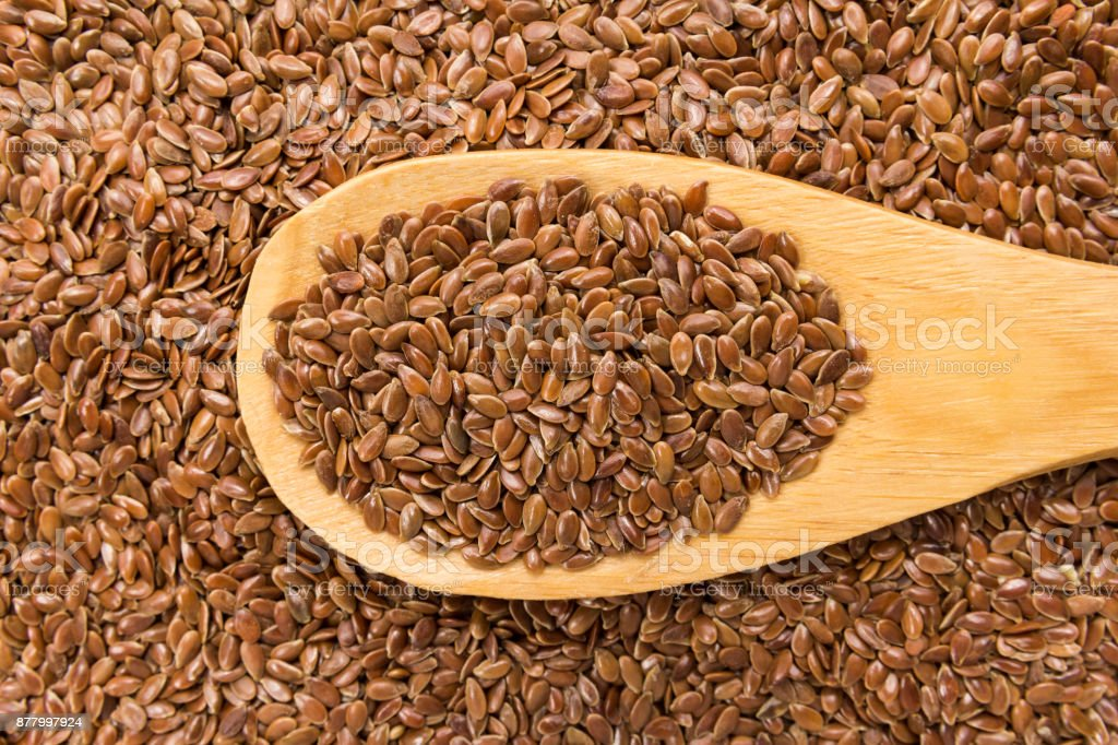 Brown Flax seed. Grains in wooden spoon. Close up. stock photo