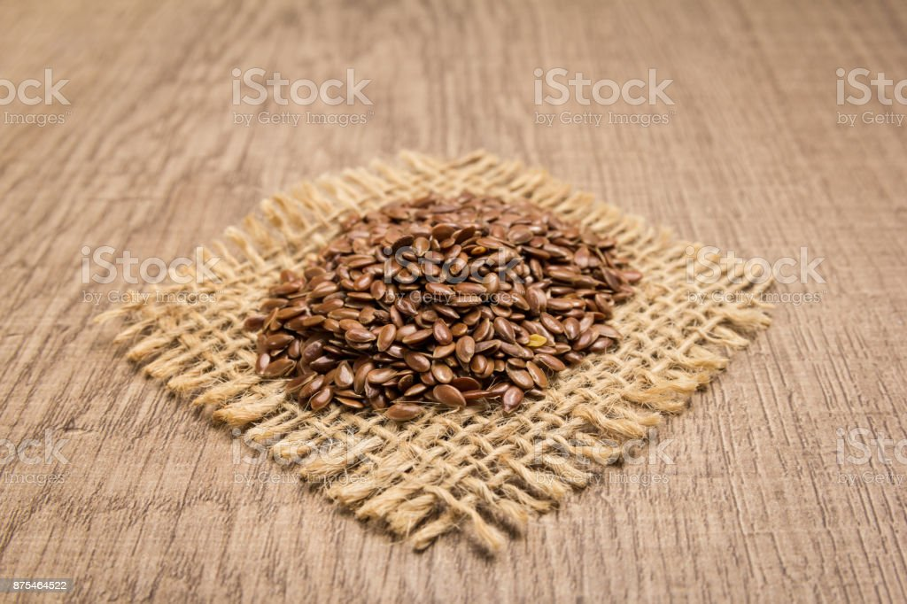 Brown Flax seed. Grains on square cutout of jute. Wooden table. Selective focus. stock photo