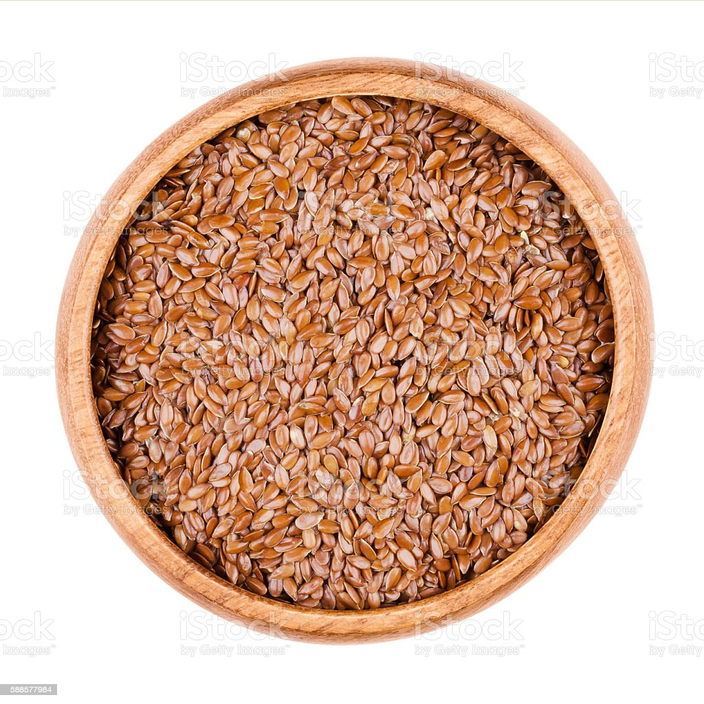 Brown flaxseeds a bowl on white background stock photo