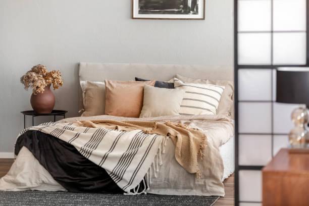 Brown flowers in pottery vase on metal nightstand next to king size bed in scandinavian bedroom interior stock photo