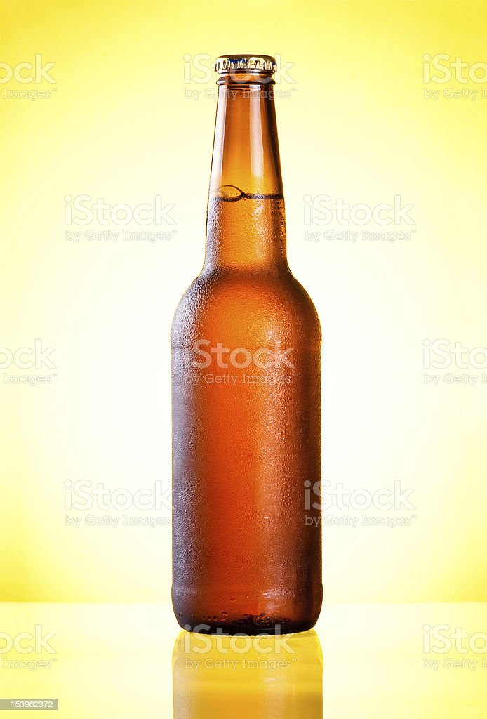 Brown full bottle fresh cold beer covered with condensate royalty-free stock photo