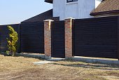 istock brown gate and wooden fence from the boards in the street 1132856264