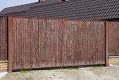 istock brown gate of wooden planks and part of the fence on a rural street 1145672990