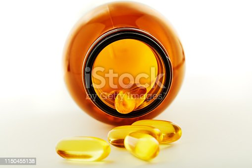 Brown glass pill bottle with some pills inside on white background