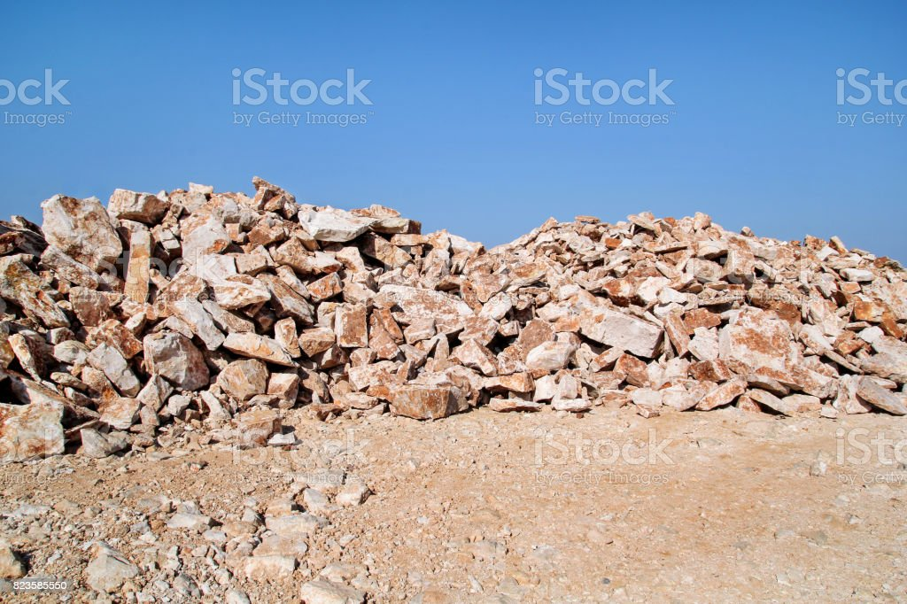 Brown Granite. Big pile of rocks for construction and boulders piled in a heap under a blue sky in summer time. A large pile of limestone in quarry. Pile of gravel and construction material. stock photo