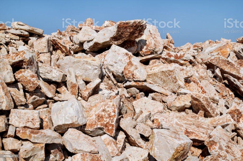 Granito marrom. Grande monte de pedras para construção e pedregulhos amontoados em uma pilha sob um céu azul no horário de verão. Uma grande pilha de calcário na pedreira. Pilha de material de construção e cascalho. - foto de acervo