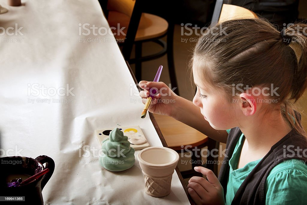 Brown Haired Girl Painting Pottery stock photo