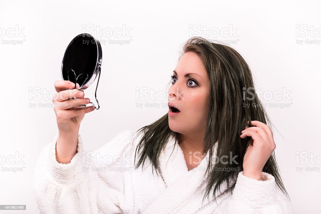 brown haired woman looking shocked at herself in a mirror stock photo