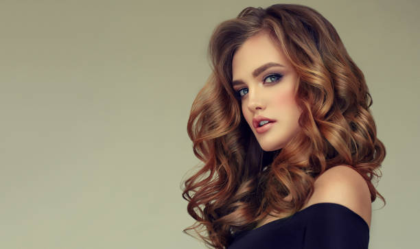Brown haired woman with voluminous, shiny and curly hairstyle.Frizzy hair. stock photo