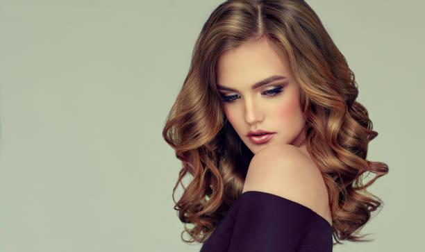 braune dunkelhaarige frau mit voluminös, glänzend und lockige frisur. krauses haar. - dauerwelle stock-fotos und bilder