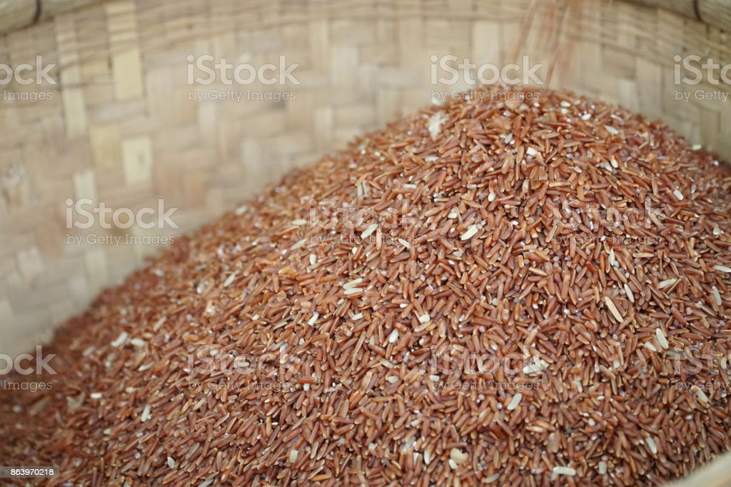 brown Jasmine rice in bamboo basket on wood background with copy space, healthy food and diet concept stock photo