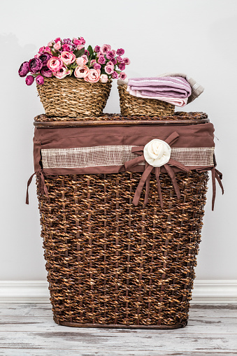 Brown knitted basket on white wooden background