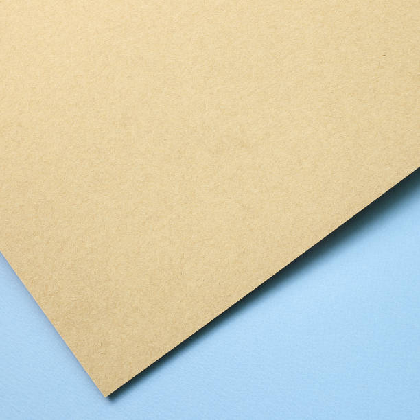 Brown kraft and blue paper sheet overlapping background stock photo