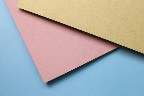 Brown kraft and pink paper and blue paper sheet overlapping background stock photo