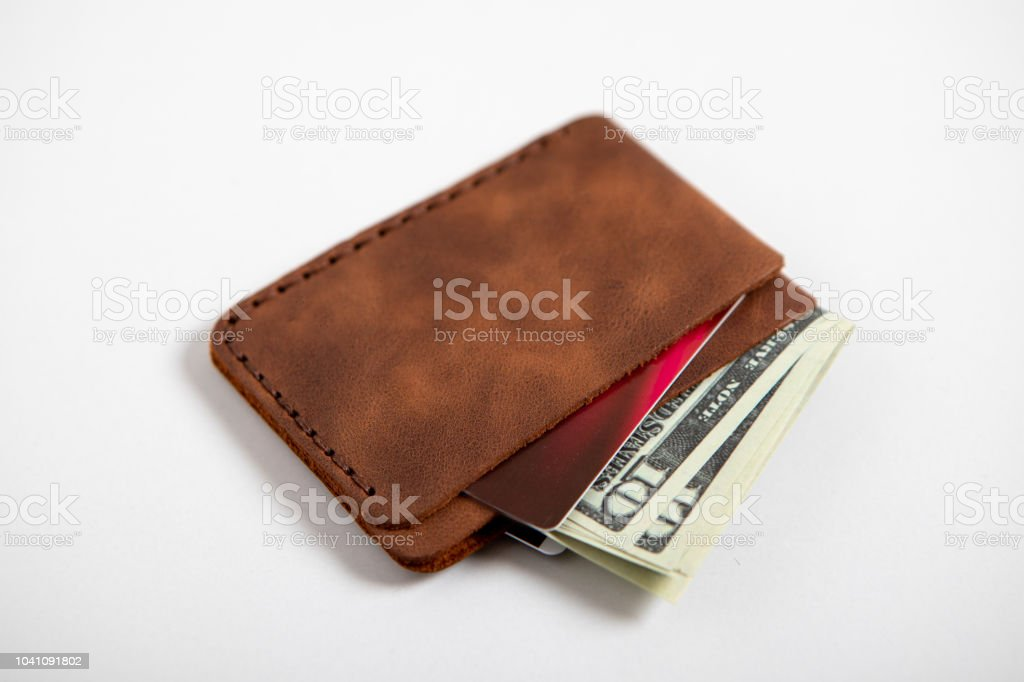 A brown leather bi-fold wallet with cash and cards stock photo
