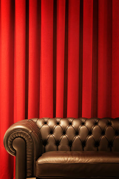 Brown Leather Couch and Red Curtains stock photo