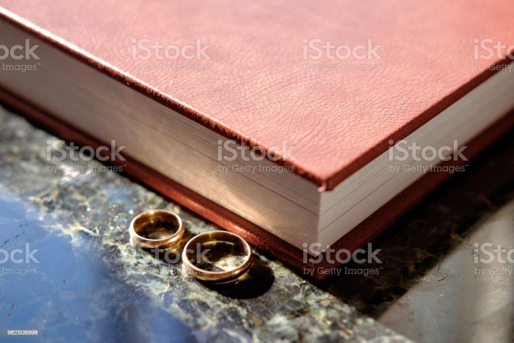 Álbum de casamento coberto de couro marrom com par de alianças de casamento ouro, cara da extremidade. - Foto de stock de Bielorrússia royalty-free