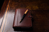istock Brown leather diary and pen on an old leather lined desk. 1305471589