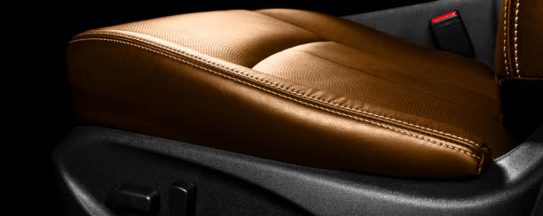 Brown leather interior of the luxury modern car. Perforated orange leather comfortable seats with stitching. Modern car interior details. Car detailing. Car inside stock photo