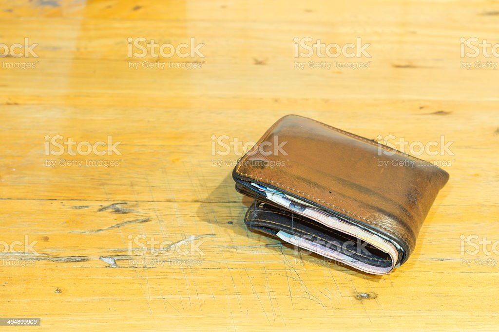 brown leather men's wallet with bank notes on brown wood texture stock photo