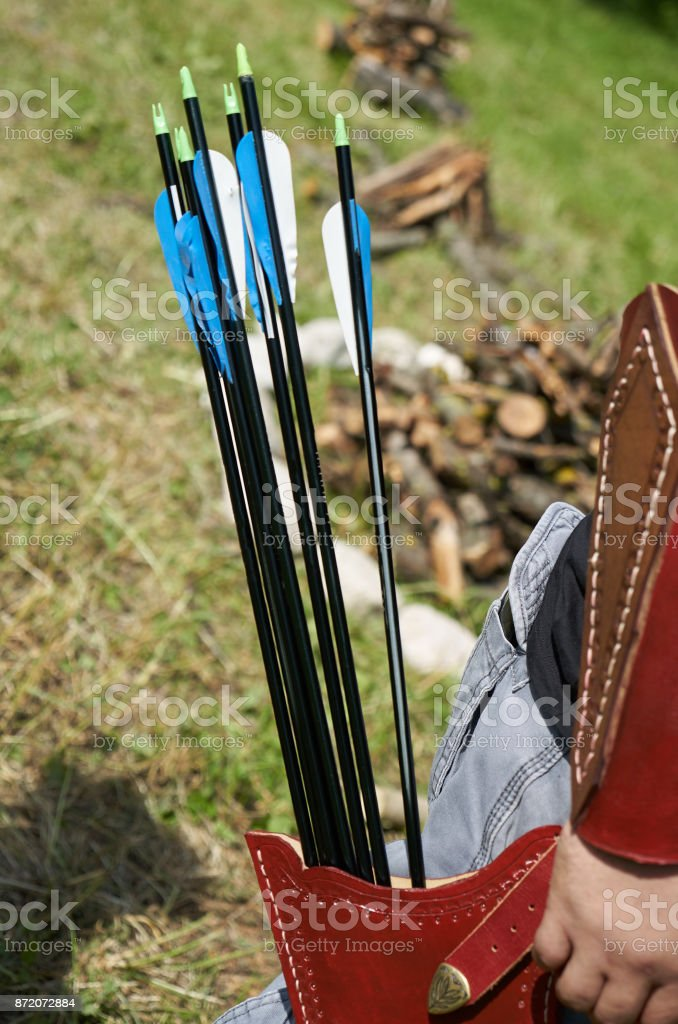Una aljaba de cuero marrón con flechas artesanales y recurve el arco en las manos del arquero - foto de stock