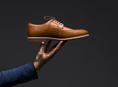 Hand holding a brown leather shoe, studio shot