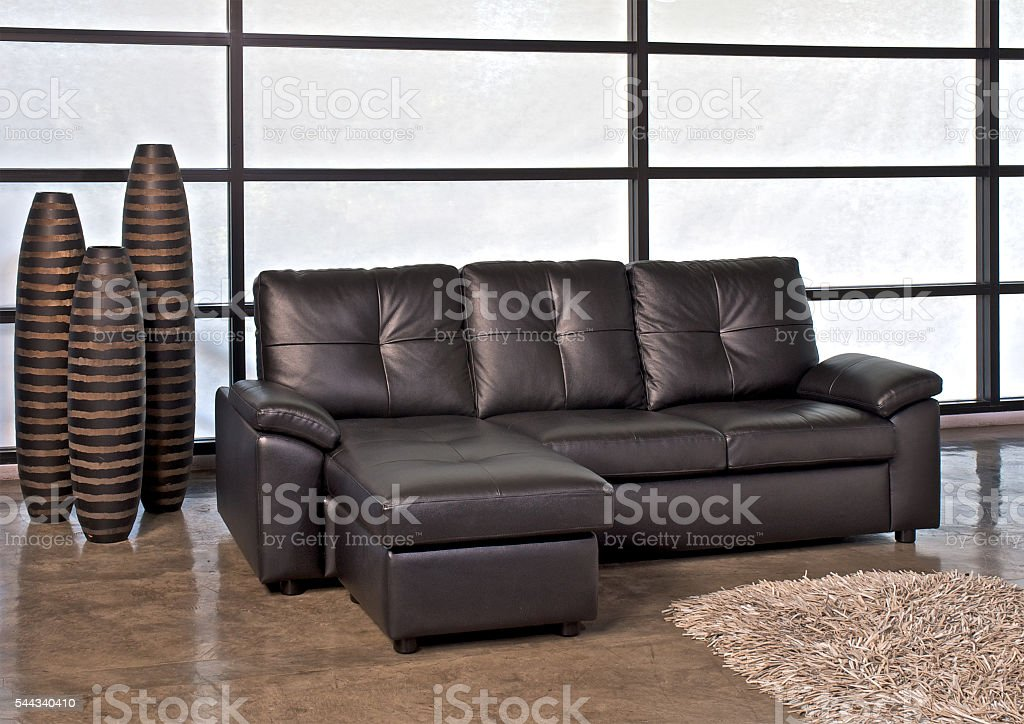 Brown leather sofa with stool – zdjęcie
