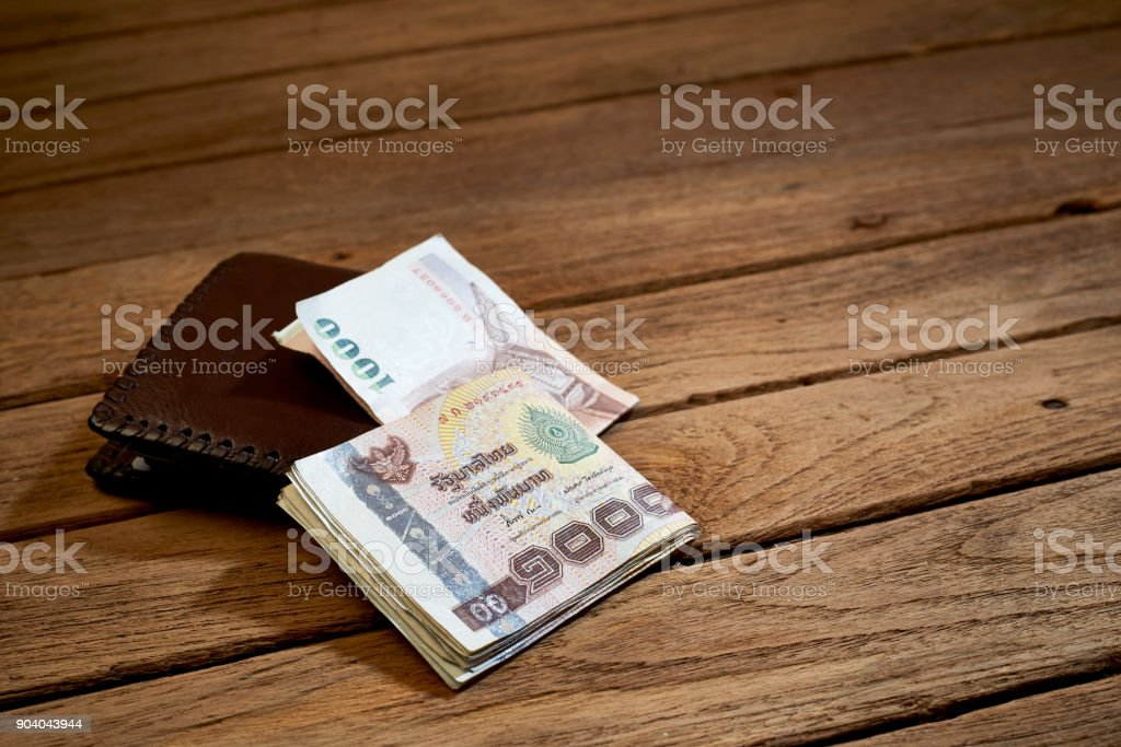 brown leather wallet and Thai money stock photo