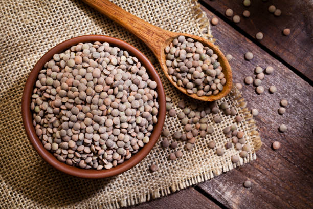 Brown lentils in a bowl stock photo