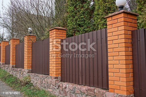 istock brown metal and brick fence outside 1187974501