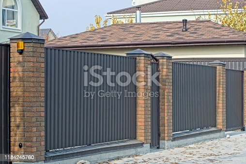 istock brown metal and brick fence 1184245760