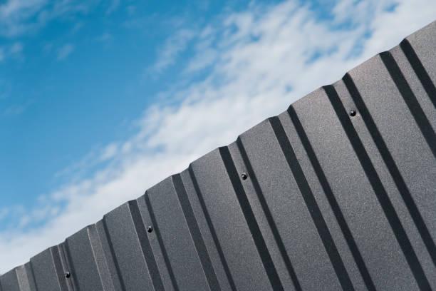 braune metallplatte gegen blauen wolkenhimmel. abstellgleis. nahtlose oberfläche aus verzinktem stahl. industriegebäude wand hergestellt aus wellpappe blech, flachen hintergrund fototexturen. - alu zaun stock-fotos und bilder