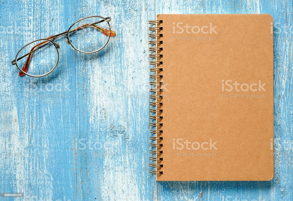 Brown notebook with glasses on blue wooden floor. royalty-free stock photo