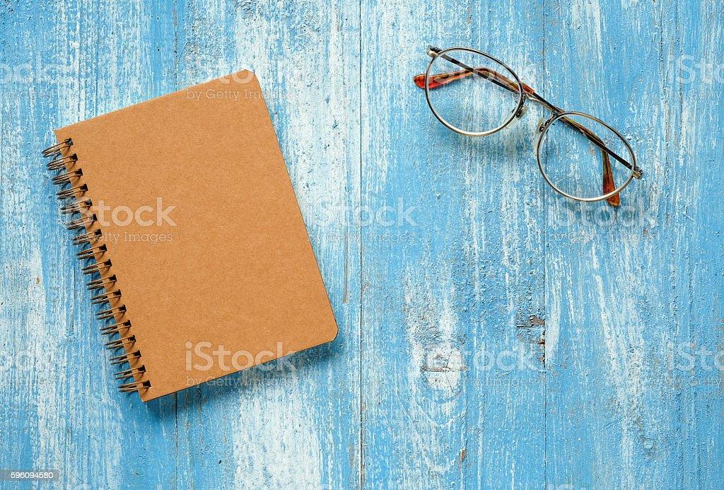 Brown notebook with glasses on blue wooden floor. Lizenzfreies stock-foto