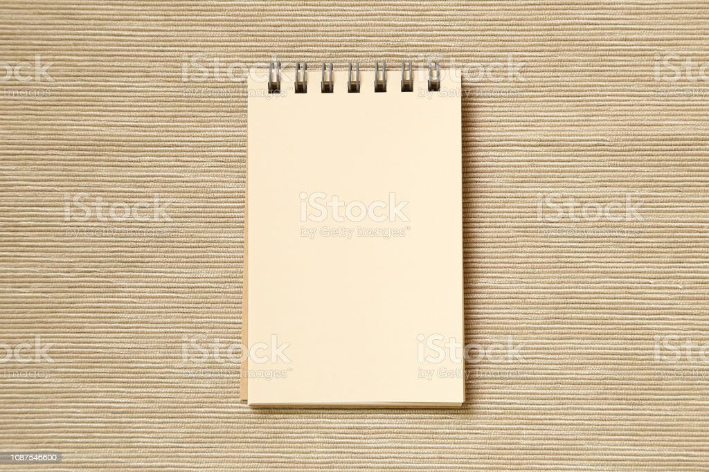 Brown notepad on beige fabric background stock photo