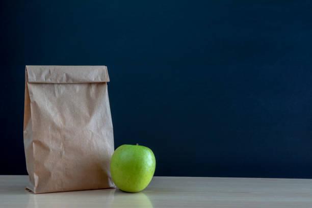 brown paper bag and  a green on blackboard background. - pasto al sacco foto e immagini stock