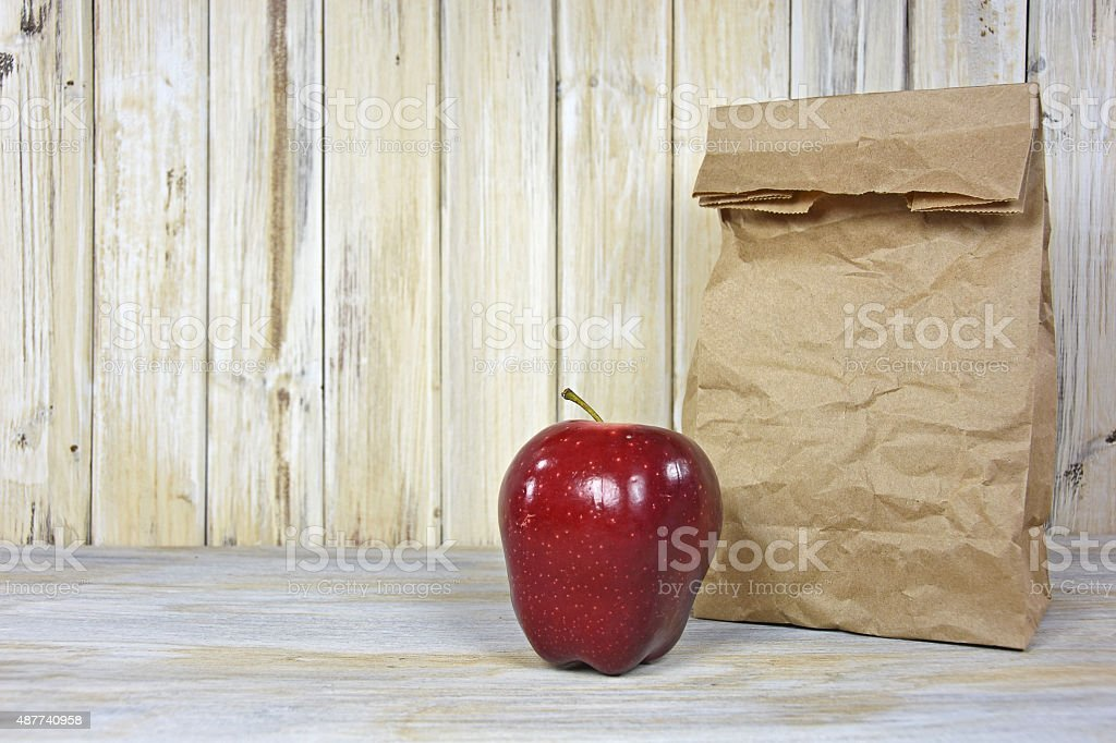brown paper bag and red apple stock photo