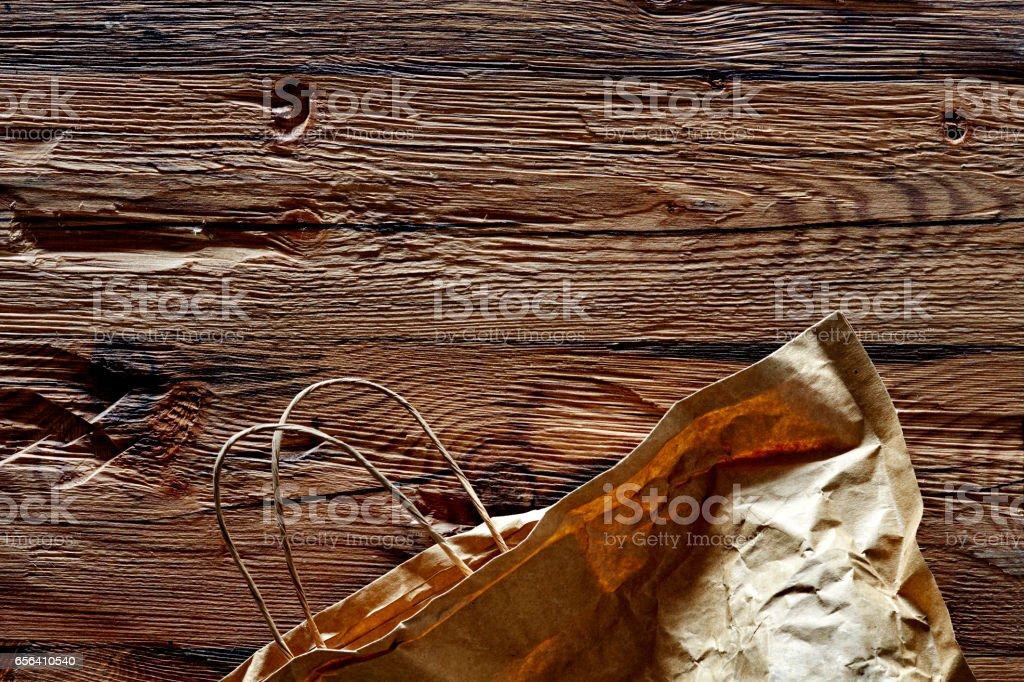 brown paper bag on wooden surface stock photo