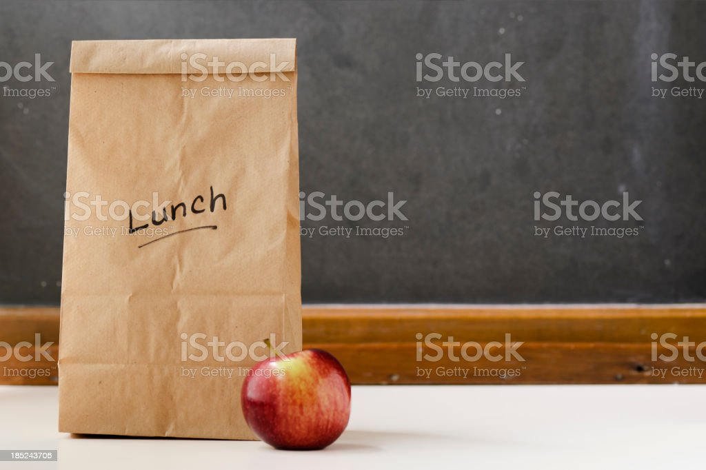 Brown paper lunch bag, red apple and chalkboard royalty-free stock photo
