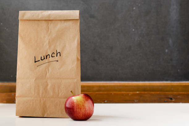 Brown paper lunch bag, red apple and chalkboard stock photo